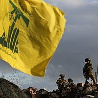 In this Dec. 13, 2018 photo, Israeli soldiers stand guard next to cameras at their new position in front of a Hezbollah flag, near the Lebanese southern border village of Mays al-Jabal, Lebanon. (AP Photo/Hussein Malla)