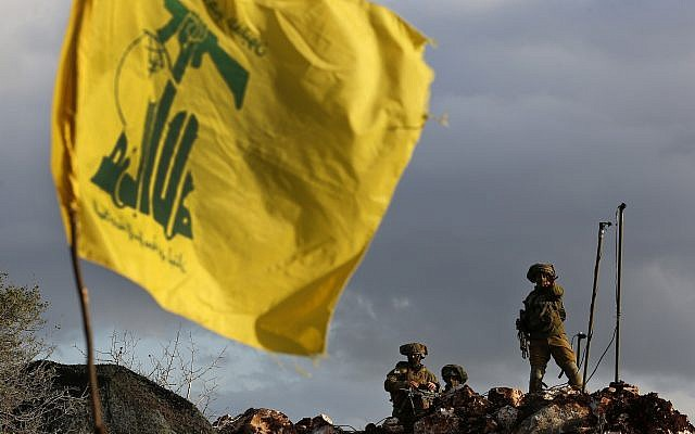 In this December 13, 2018 photo, Israeli soldiers stand guard next to cameras at their new position in front of a Hezbollah flag, near the Lebanese southern border village of Mays al-Jabal, Lebanon. (AP Photo/Hussein Malla)