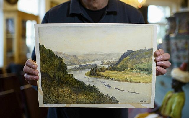 An employee of an action house holds a watercolor landscape, allegedly painted by a young Adolf Hitler but of uncertain origin, in Berlin, Germany, January 24, 2019. (Gregor Fischer/dpa via AP)