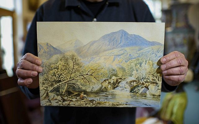 An employee of an action house holds a watercolor landscape, allegedly painted by a young Adolf Hitler, in Berlin, Germany, January 24, 2019. (Gregor Fischer/dpa via AP)