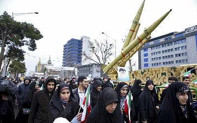 Iranians walk past a missile during a rally marking the 40th anniversary of the 1979 Islamic Revolution, in Tehran, Iran, Monday, Feb. 11, 2019. (AP/Ebrahim Noroozi)