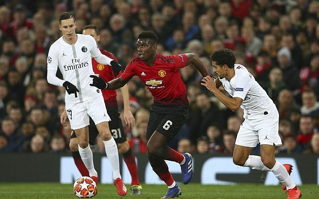 Manchester United's Paul Pogba, centre, vies for the ball with Paris Saint Germain's Marcos Marquinhos, right, during the Champions League round of 16 soccer match between Manchester United and Paris Saint Germain at Old Trafford stadium in Manchester, England, Tuesday, Feb. 12,2019.(AP Photo/Dave Thompson)