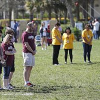 People at Trails End Park pause for a moment of silence in honor of the 17 that were killed during the Marjory Stoneman Douglas High School shooting last year, Thursday, Feb. 14, 2019, in Parkland, Fla. (AP/Wilfredo Lee)