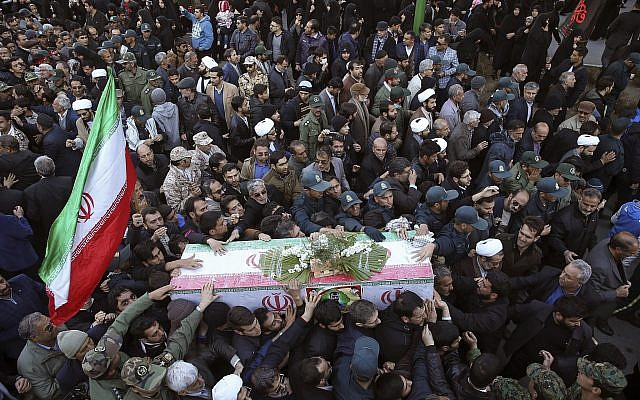 Mourners a carry flag-draped casket during a mass funeral for those killed in a suicide car bombing that targeted members of Iran's Revolutionary Guard in Isfahan, killing at least 27 people. (AP Photo/Ebrahim Noroozi)