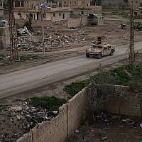 A Humvee drives in a village recently retaken from Islamic State militants by US-backed Syrian Democratic Forces (SDF) near Baghouz, Syria on February 17, 2019, (AP Photo/Felipe Dana)