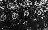 SS members carry flags with a swastika and names of German states and towns as they march towards the town hall of Nuremberg, Germany, September 10, 1935, to open the convention of the National Socialist German Workers' Party. (AP Photo)