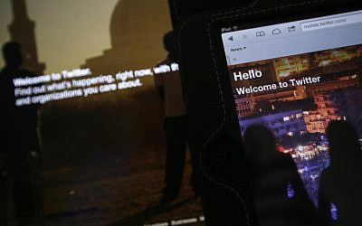 In this July 31, 2013 photo, the home page for Twitter is displayed on an iPad and a laptop computer. (AP Photo/Alastair Grant)