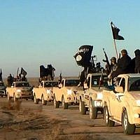 In this undated file photo released online in the summer of 2014 on a militant social media account, which has been verified and is consistent with other AP reporting, terrorists of the Islamic State group hold up their weapons and wave its flags on their vehicles in a convoy on a road leading to Iraq, in Raqqa, Syria. (Militant photo via AP, File)