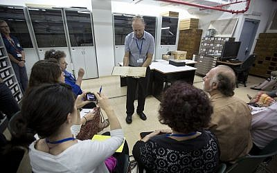 Yad Vashem's archive director Haim Gertner shows a document to visiting international experts and others who are participating in a workshop devoted to the physical and digital preservation of documents, in Jerusalem, September 2014. (AP Photo/Sebastian Scheiner)