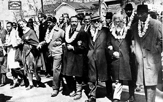 Dr. Martin Luther King Jr. links arms with other civil rights leaders as they begin the march to the state capitol in Montgomery from Selma, Alabama, on March 21, 1965. The demonstrators are marching for voter registration rights for blacks. Accompanying Dr. Martin Luther King Jr. (fourth from right), are on his left Ralph Bunche, undersecretary of the United Nations, Rabbi Abraham Joshua Heschel, and Rev. Fred Shuttlesworth. They are wearing leis given by a Hawaiian group. (AP Photo)