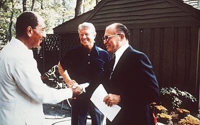 Egypt's president Anwar Sadat, left, shakes hands with Israeli prime minister Menachem Begin, right, as US president Jimmy Carter looks on, in September 1978. (AP)