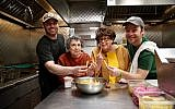 Sheila (center left) and Marilynn Brass learn to make cheeseburgers at Mainely Burgers in Cambridge, Massachusetts from Jack Barber (far left) and Max Barber (right). (Bruce Seidel)