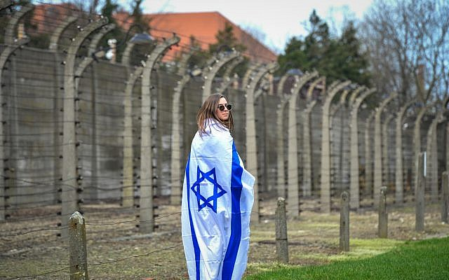 A woman wrapped in an Israeli flag at the March of the Living at the Auschwitz-Birkenau camp site in Poland, April 11, 2018 (Yossi Zeliger/Flash90)