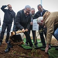 Prime Minister Benjamin Netanyahu plants an olive tree at the Netiv Haavot settlement in the West Bank, on January 28, 2019. (Marc Israel Sellem/POOL)