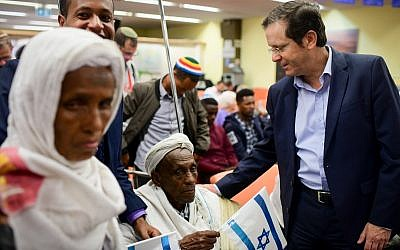 Jewish Agency Chairman Isaac Herzog welcomes members of the Falashmura community as they arrive at the Immigration offices at Ben Gurion Airport on February 4, 2019. (Tomer Neuberg/Flash90)