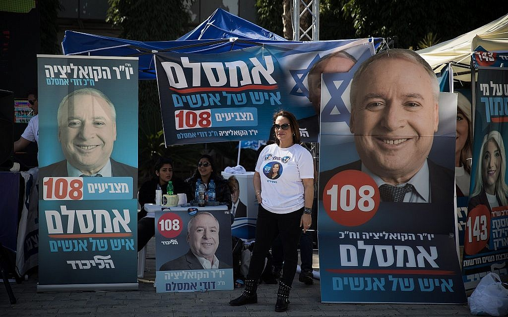 Likud supporters campaign for party member David Amsalem  outside Tel Aviv Likud polling station on February 5, 2019 (Hadas Parush/Flash90)
