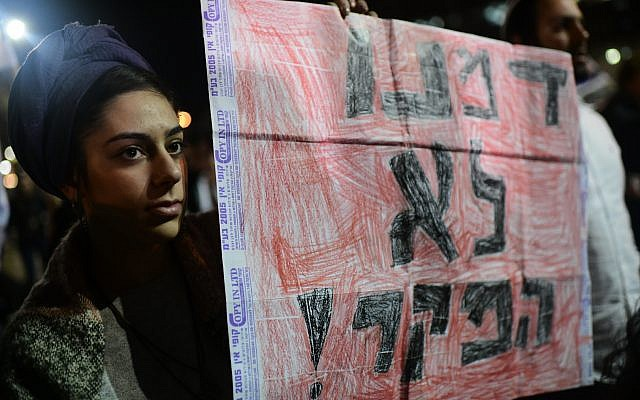 An Israeli woman holds a sign reading 'Our blood is not worthless,' during a rally in Tel Aviv on February 9, 2019, following the murder of 19-year-old Ori Ansbacher. (Tomer Neuberg/Flash90)
