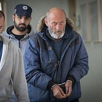Valery Sakovich, suspect in the murder case of a young woman in 1993, escorted by police to a hearing at Jerusalem Magistrate's Court on February 6, 2019. (Noam Revkin Fenton/Flash90)