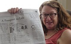 Heidi Fishman holding up an op-ed she wrote about her family's rescue from the Holocaust using a Paraguayan passport. (Courtesy of Fishman via JTA)