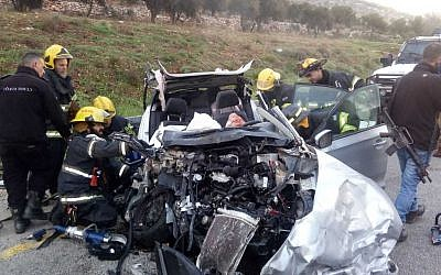 Firefighters at the scene of a deadly car crash in the central West Bank on February 19, 2019. (Israel Police)