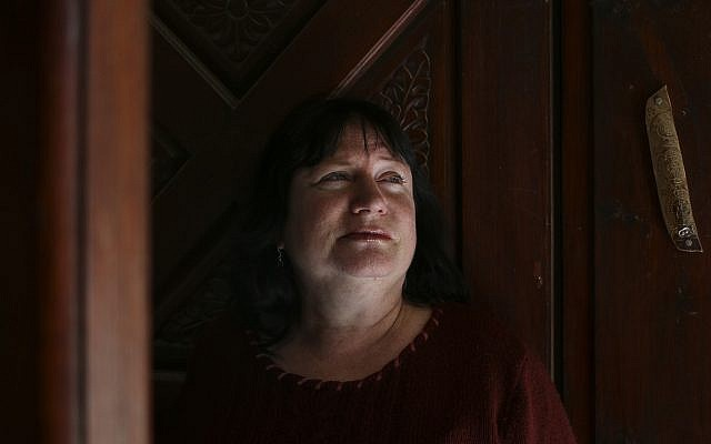 Riki Eyal stands in front of the door of her home in Arad (Johanna Chisholm/Times of Israel)