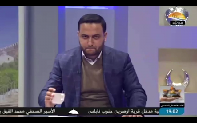 A newscaster on the Hamas-affiliated Al-Aqsa television station places a mug on his desk in what the Shin Bet security service says was a secret code to an operative in the West Bank. (Screen capture: Al-Aqsa TV/Shin Bet)