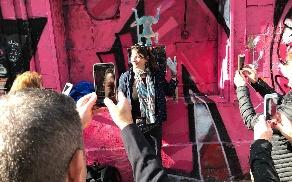 Shiry Avny in front of a stencil she spray painted during her street art demonstration near the end of her tour. (Robert Sarner/ Times of Israel)