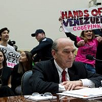 US Special Representative for Venezuela Elliott Abrams testifies as demonstrators protest behind him during the House Foreign Affairs subcommittee hearing on Venezuela at Capitol Hill in Washington, February 13, 2019. (AP Photo/Jose Luis Magana)
