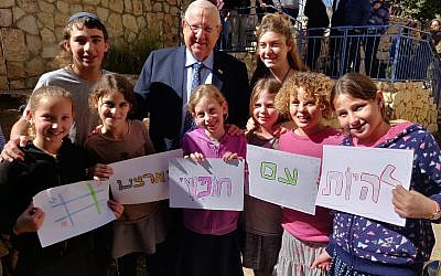 "President Reuven Rivlin (c) stands with a group of children holding signs that read ""to be a free people on our land,"" after paying a condolence visit at the home of Ori Ansbacher's family in the Tekoa settlement on February 13, 2019. (Courtesy)"