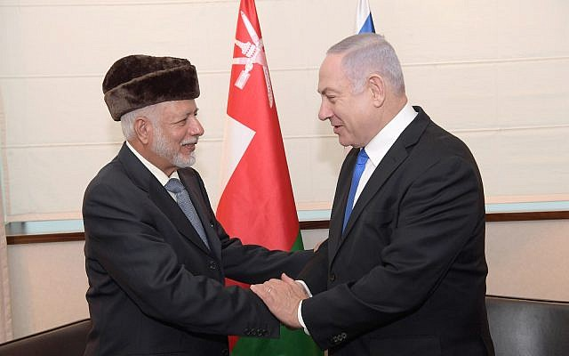 Prime Minister Benjamin Netanyahu (right) greets Omani Foreign Minister Yusuf bin Alawi bin Abdullah at the sidelines of a regional conference on the Middle East in Warsaw, February 13, 2018 (Amos Ben Gershom/GPO)