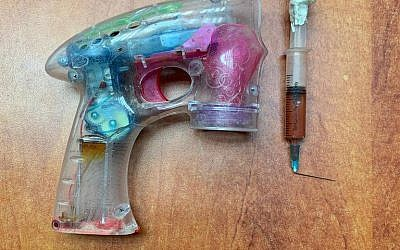 A soap bubble gun and syringe allegedly used by a Jordanian citizen to hold up an Israeli postal bank in January 2019. (Israel Police)