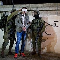 Illustrative. IDF soldiers handcuffing and blindfolding a Palestinian during an operation to arrest terror suspects in the West Bank, December 8, 2015. (Nati Shohat/Flash90.)