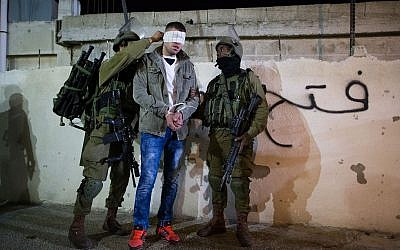 Illustrative photo of IDF soldiers handcuffing and blindfolding a Palestinian during an operation to arrest terror suspects in West Bank, December 8, 2015. (Nati Shohat/Flash90.)