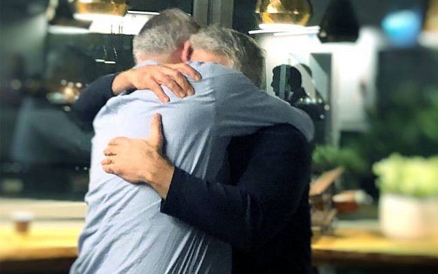 Benny Gantz and Yair Lapid embrace after deciding to forge an alliance for the upcoming election, February 21, 2019. (Courtesy/Facebook)