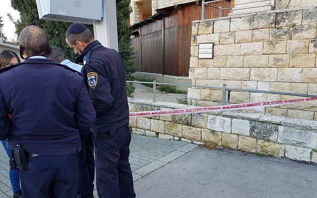 Police officers question a passerby near a bus stop in Jerusalem's Gilo neighborhood following Sunday morning's stabbing incident. (Israel Police)