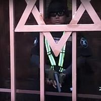 A guard seen outside a Jewish school and synagogue in Los Angeles before shooting the person filming the scene in the leg, on February 14, 2019. (screen capture: YouTube)