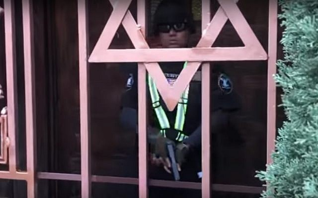 A guard seen outsided a Jewish school and synagogue in Los Angeles before shooting the person filming the scene in the leg, on February 14, 2019. (screen capture: YouTube)