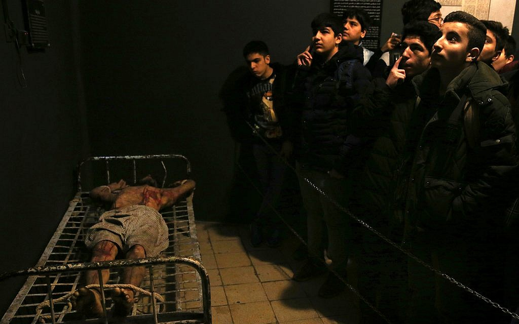 Iranian schoolboys look at an exhibition at a former prison run by the pre-revolution intelligence service, SAVAK, now a museum, where a wax mannequin of a prisoner is tied to a bed, in downtown Tehran, Iran, January 7, 2019. (AP Photo/Ebrahim Noroozi)