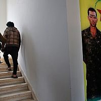 A Kurdish prison security guard, left, escorts a 19-year-old former fighter of the Islamic State group, into the courtroom of a Kurdish-run terrorism court, in Qamishli, north Syria, April 3, 2018. (AP Photo/Hussein Malla)