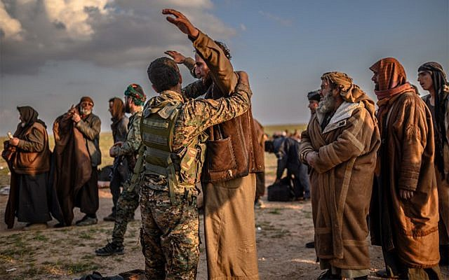 Men suspected of being Islamic State fighters are searched by members of the Kurdish-led Syrian Democratic Forces (SDF) after leaving the Islamic State's last holdout of Baghouz in Syria's northern Deir Ezzor province, February 22, 2019.  (Bulent Kilic/AFP)