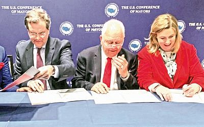 Signing the agreement on Jan. 24 between the American Jewish Committee and the US Conference of Mayors for AJC to host annual trips to Israel for US mayors (L to R): AJC CEO David Harris, Conference of Mayors CEO Tom Cochran, and Conference of Mayors International Committee Chair Nan Whaley, Mayor of Dayton. (US Conference of Mayors/ via Dayton Jewish Observer)