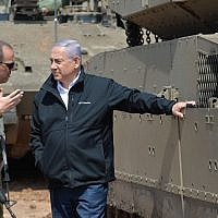 Illustrative: Prime Minister Benjamin Netanyahu, right, speaks with an IDF officer near the border with the Gaza Strip on March 28, 2019. (Kobi Gideon/GPO)