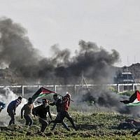 Palestinians holding Palestinian flags walk past burning tires during clashes near the security fence along the border with Israel, east of Gaza City, on February 22, 2019. (Mahmud Hams/AFP)