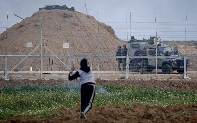 A Palestinian uses a slingshot to hurl objects towards Israeli forces next to an armored vehicle on the other side of the barbed-wire fence, at the border with Israel east of Gaza City on March 1, 2019. (Photo by Said KHATIB / AFP)