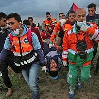 Illustrative: Palestinian paramedics carry away on a stretcher a youth injured during clashes following a demonstration along the border with Israel east of Gaza City on March 1, 2019. (SAID KHATIB / AFP)