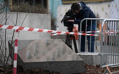 A cameraman films the memorial stone marking the site of Strasbourg's Old Synagogue, which was destroyed by the Nazis in World War II, after it was vandalized overnight on March 2, 2019 in Strasbourg, eastern France (FREDERICK FLORIN / AFP)