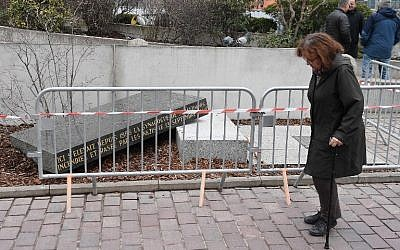 A person passes by the memorial stone marking the site of Strasbourg's Old Synagogue, which was destroyed by the Nazis in World War II, after it was vandalised overnight on March 2, 2019 in Strasbourg, eastern France. (FREDERICK FLORIN / AFP)