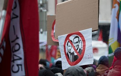 A protester holds a sign depicting Austria's Chancellor Sebastian Kurz, left, and Austrian Vice Chancellor Heinz-Christian Strache during a rally in Vienna, December 15, 2018. (ALEX HALADA/AFP)