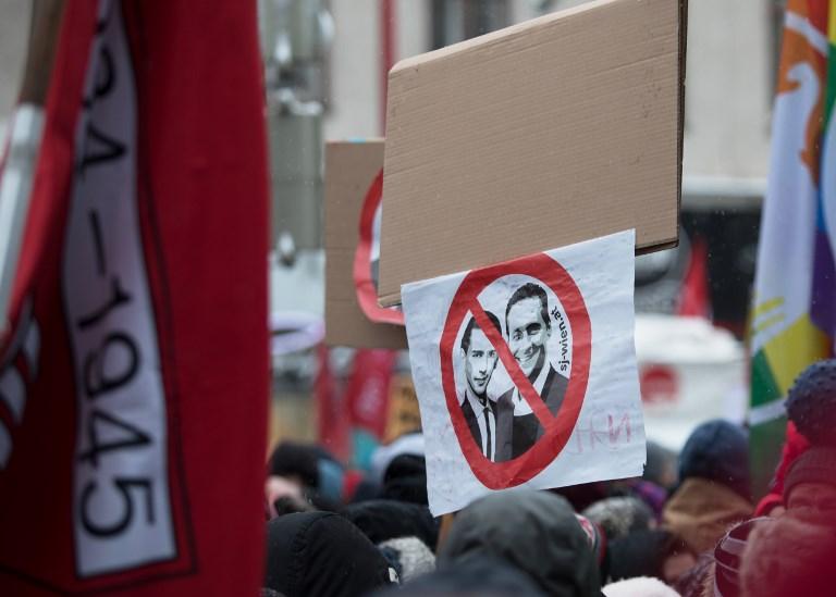 6f619e0320e A protester holds a sign depicting Austria's Chancellor Sebastian Kurz,  left, and Austrian Vice