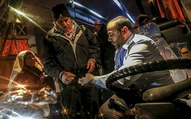 A Hamas police officer checks the travel documents of incoming Muslim pilgrims boarding a bus at the Rafah border crossing between the Gaza Strip and Egypt on March 3, 2019. (SAID KHATIB / AFP)